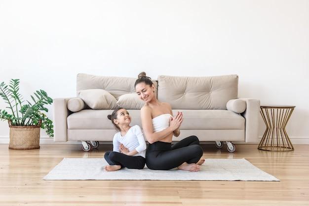 요기 여자와 아이는 거실에서 집에서 요가 연습