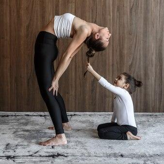 Женщина-йог и дочь-ребенок вместе занимаются йогой и растяжкой, занимаясь спортом