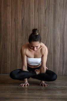 Yogi woman doing cock pose in yoga