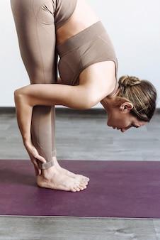 Женщина йога делает растяжку и йогу, стоя на коврике