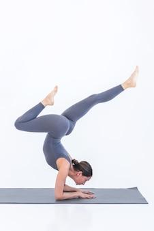 Yogi woman doing yoga standing on elbows in pose on white background