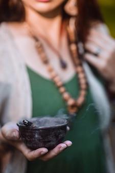 그녀의 손에 흡연 그릇을 들고 요기 여자