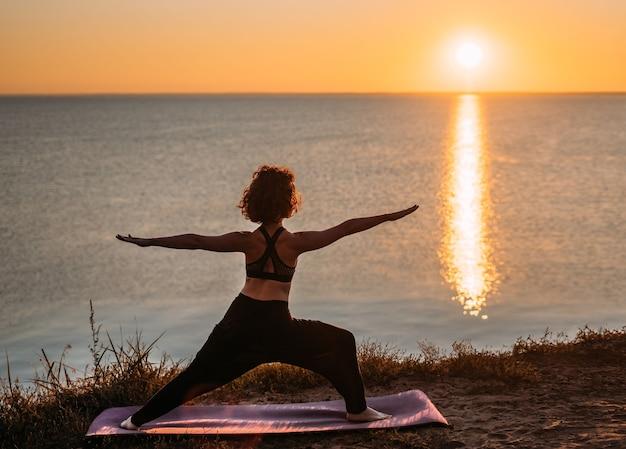 ヨギの女性は海のそばの日の出でヨガを練習します Premium写真