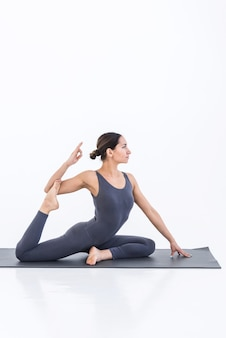 Yogi woman practicing sport yoga on white scene