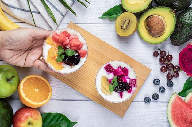 Йогурт и фрукты на доливе в стакане с различными фруктами на обоях белого деревянного стола, фоне фруктов. здоровое диетическое питание. вид сверху