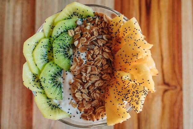 キウイやパイナップルなどのフルーツ、チア、ドライフルーツ、カリカリのミューズリーが入ったヨーグルトボウル。