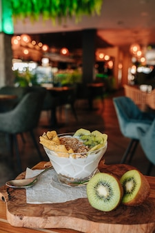 Yogurt bowl with fruits such as kiwi and pineapple, chia, dried fruits and crunchy muesli.
