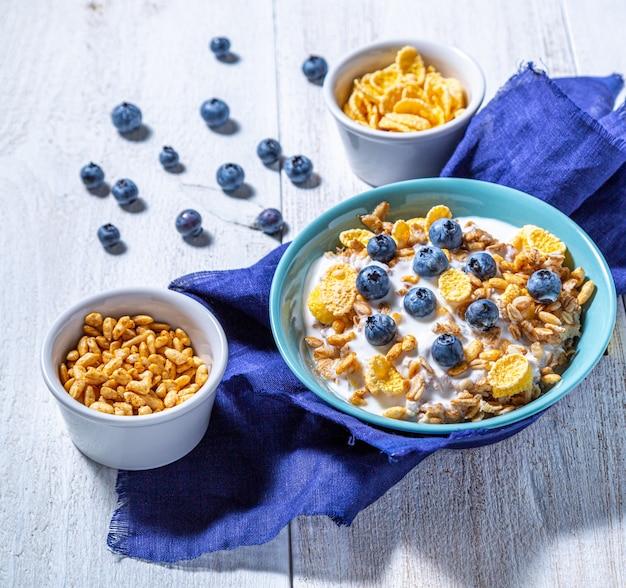 Йогурт, миски с мюсли, черникой, кукурузными хлопьями и воздушным рисом на белой поверхности. здоровый завтрак