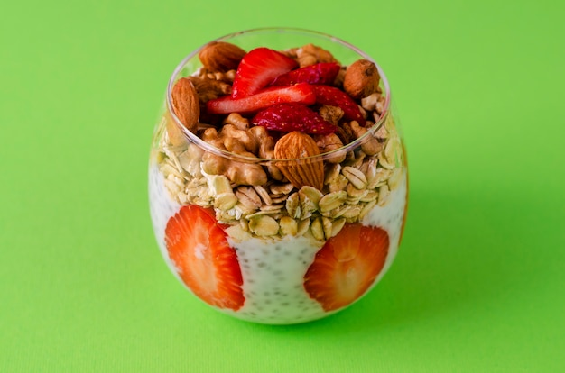 Yogurt chia pudding with fresh strawberries, oats and nuts in a glass on green