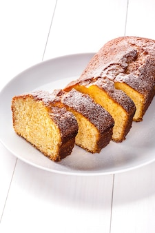Yogurt citrus cake with powdered sugar on top. cake on a white plate on a wooden background