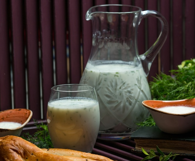 Yogurt cold drink with mint and herbs inside in a glass and a jar