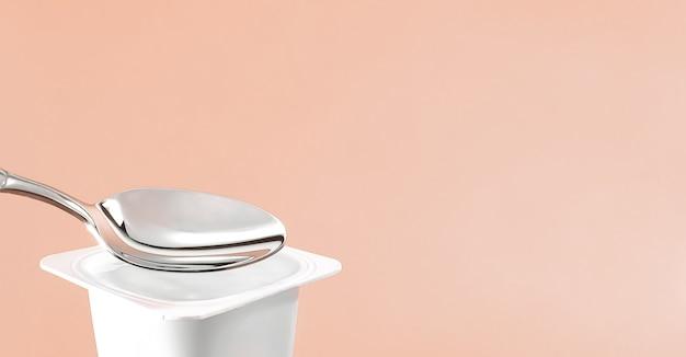 健康的な食事と栄養バランスのためのヨーグルトクリーム新鮮な乳製品とベージュの背景の白いプラスチック容器にヨーグルトカップと銀のスプーン