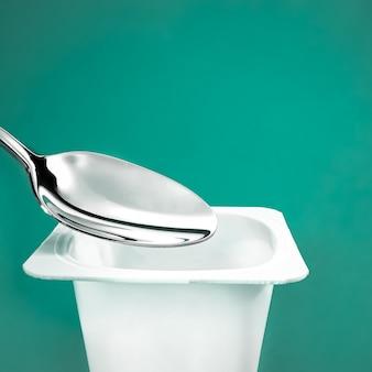 Чашка для йогурта и серебряная ложка на зеленом фоне белый пластиковый контейнер с йогуртовым кремом fresh dai ...