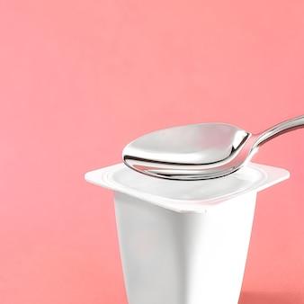 ピンクの背景にヨーグルトカップと銀のスプーン、ヨーグルトクリームの新鮮なdairと白いプラスチック容器...