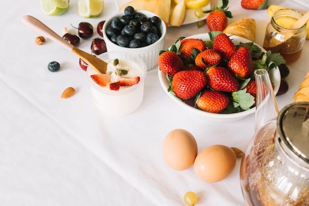 Yogurt; egg; teapot and fruits on white backdrop