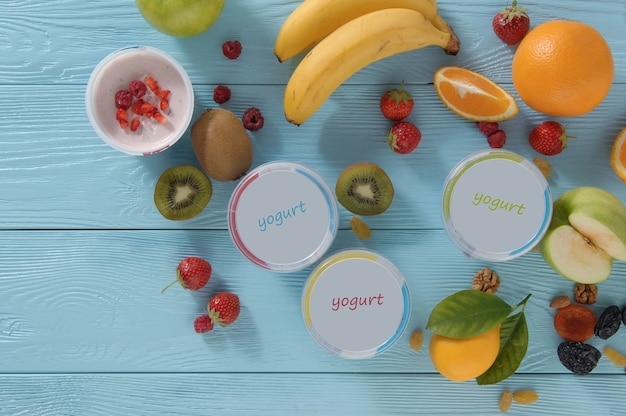 Йогурт в контейнере с тропическими фруктами на деревянном фоне, вид сверху. концепция здорового питания