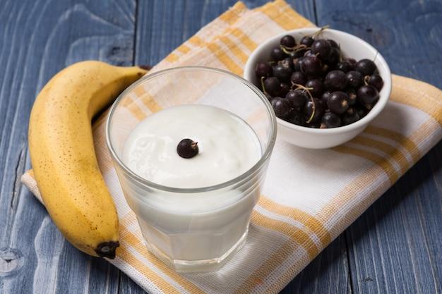 Йогурт в стакане, банан и смородина на деревянных досках