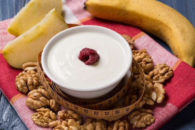 Йогурт в пиале, украшенный малиной, орехами и фруктами, концепция здорового питания