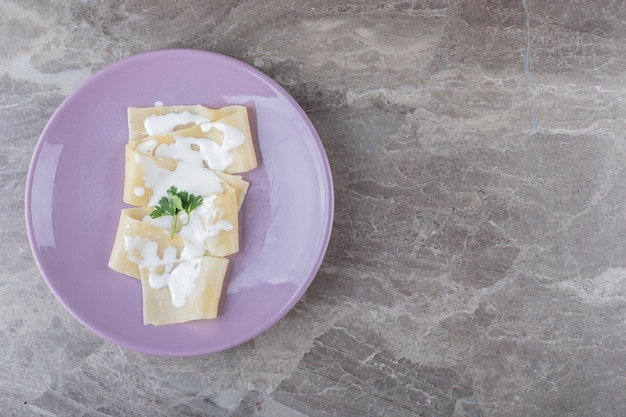 Йогурт на листах лазаньи с зеленью на тарелке, на мраморной поверхности.