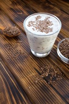 Йогурт или кефир с семенами льна в стакане на коричневом деревянном фоне. расположение вертикальное. скопируйте пространство.