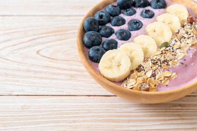 Йогурт или миска для смузи из йогурта с синей ягодой, бананом и мюсли - стиль здорового питания