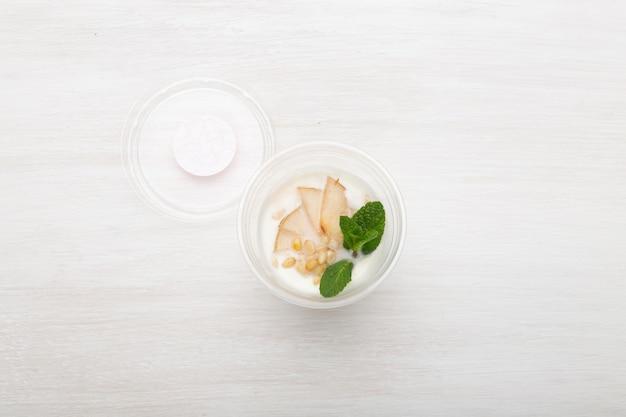 Ломтики йогурта, груши, мяты и кедровые орехи лежат в коробке для завтрака на белом столе рядом с разбросанными