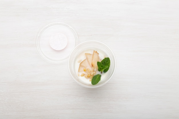 Yogurt pear slices and mint and pine nuts lie in a lunch box on a white table next to scattered with