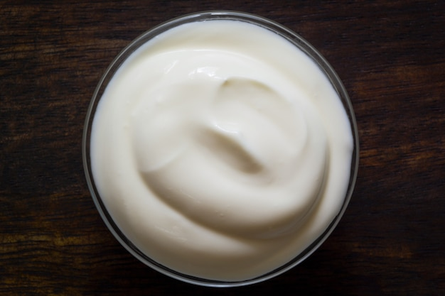 Yogurt or sour cream in a glass bowl on wood