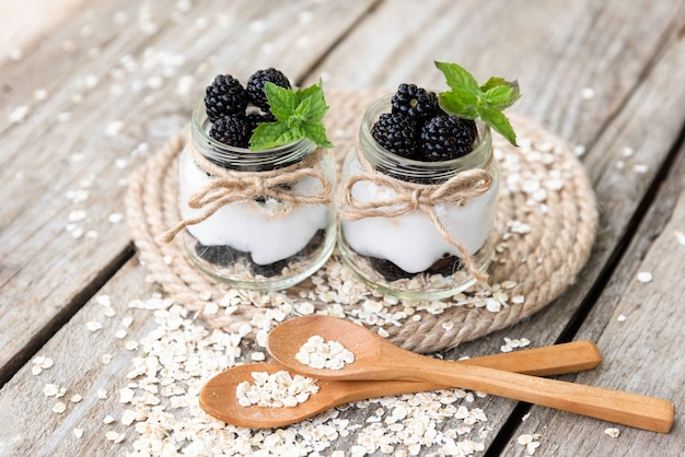 Yogurt with blackberries in glass jars made from natural products.