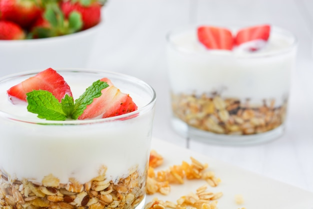 Yogurt with cereals and strawberries on white wooden table
