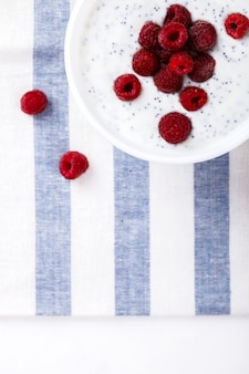 Yogurt with chia seeds and fresh raspberries.summer breakfast