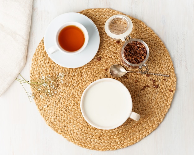 Yogurt with chocolate granola in cup, breakfast with tea on beige background, top view.