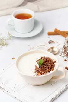 Yogurt with chocolate granola in cup, breakfast with tea on white wooden background, vertical.