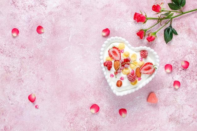 콘플레이크와 딸기를 하트 모양의 그릇에 담은 요구르트.