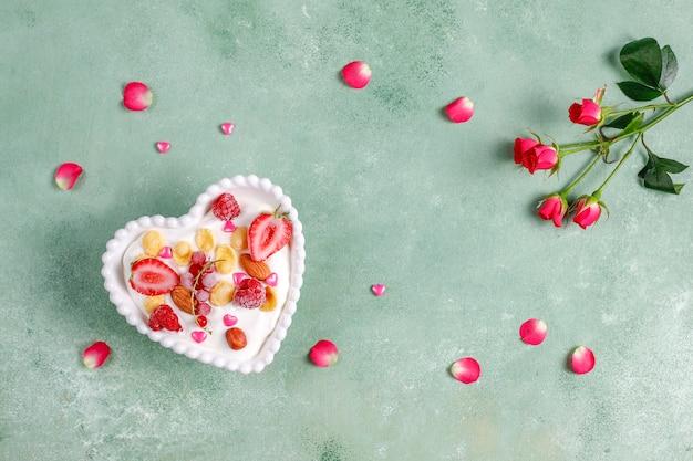 Йогурт с кукурузными хлопьями и ягодами в миске в форме сердца.