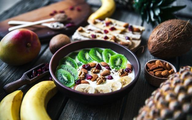 Йогурт с разными фруктами на деревянном столе. полноценное питание, диетическое, органическое.