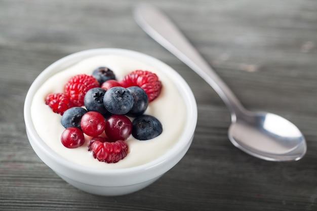 Йогурт с лесными ягодами на деревянном столе