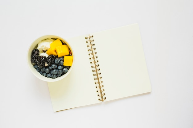 Yogurt with mango slices; blueberry and blackberry toppings in cup on spiral notebook