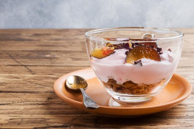 Йогурт с мюсли и ягодами в маленьком стакане.