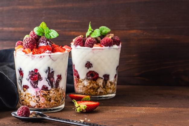 Йогурт с мюсли и ягодами в двух стаканах на темном деревянном столе