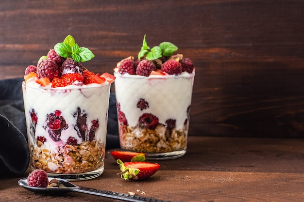 Yogurt with muesli and berries in two glasses on dark wooden table