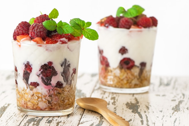 Yogurt with muesli and berries in two glasses on light wooden table