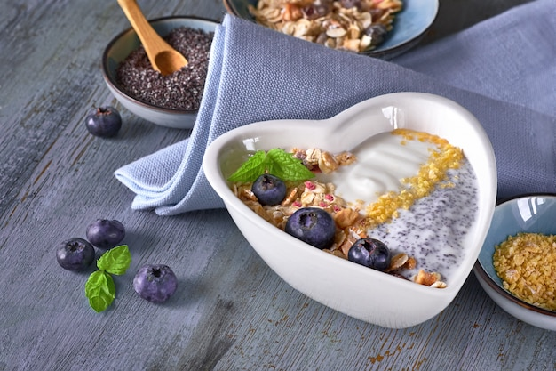 Yogurt with muesli, blueberries, poppy seeds, mint and crushed cornflakes served in heart-shaped bowl