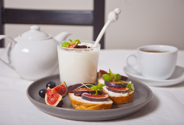 Yogurt with muesli and fig fruit in a glas and sandwich with cream cheese, figs and honey