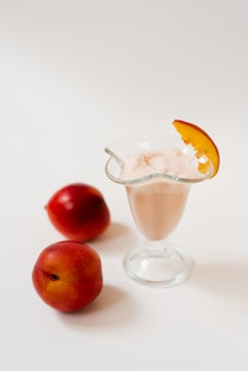 Yogurt with nectarines in a glass, next to fresh organic nectarines. the concept of healthy and delicious food
