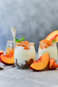 桃のジャムと丸いガラスの瓶に新鮮な桃とヨーグルト、デザートのレシピ。ヘルシーな朝食