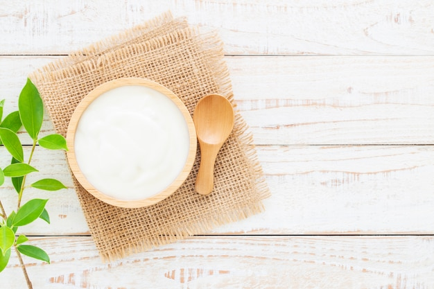 Yogurt in wood bowl on white wooden table healthy food concept