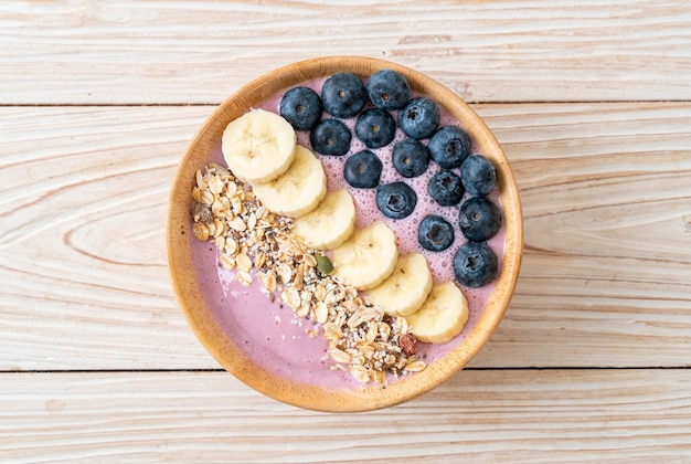 Yogurt or yoghurt smoothie bowl with blue berry, banana and granola - healthy food style