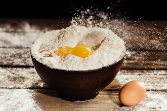 Yolks falling into bowl with flour on wooden table with one egg near