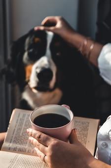 かわいいバーニーズ・マウンテン・ドッグの犬と一緒に居間に座って、コーヒーを読んだり飲んだりしているヨーマン。